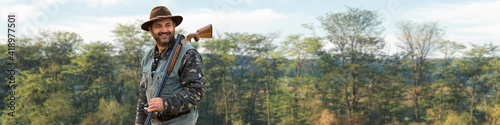 Fotografia A hunter with a gun in his hands in hunting clothes in the autumn forest in search of a trophy