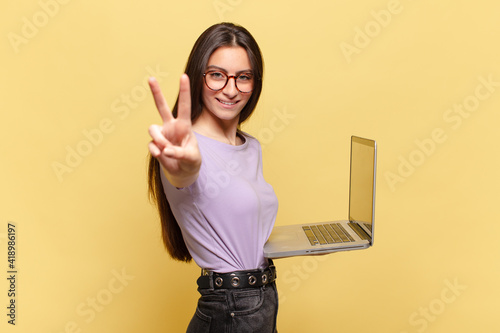 Obraz young pretty woman smiling and looking happy, carefree and positive, gesturing victory or peace with one hand. laptop concept - fototapety do salonu