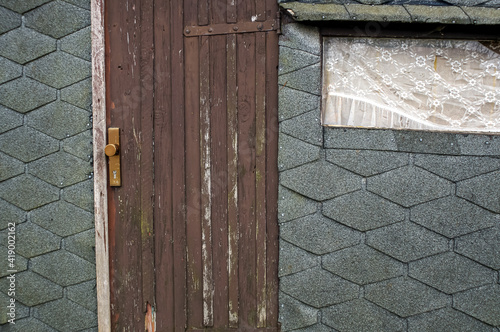 Canvas old wooden door and a window on a boathouse with tar paper
