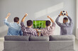 Leinwandbild Motiv Four adult male friends with arms raised emotionally watching a football match on TV at home. Unrecognizable friends sit on the couch with their backs to the camera and cheer for their favorite team.