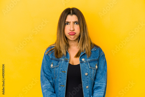 Valokuva Young indian woman isolated on yellow background blows cheeks, has tired expression