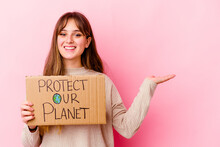 Young Caucasian Woman Holding A Protect Our Planet Placard Isolated Showing A Copy Space On A Palm And Holding Another Hand On Waist.