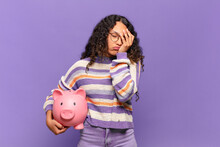 Young Hispanic Woman Feeling Bored, Frustrated And Sleepy After A Tiresome, Dull And Tedious Task, Holding Face With Hand. Piggy Bank Concept