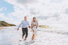 Happy Just Married Middle Age Couple Walk At Beach Against Blue Sky With Clouds And Have Fun At Summer Day. Togetherness, Love, Family