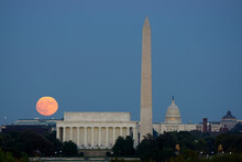 Large Full Moon Rises Through The Haze Over The Capitol Building In Washington DC With Lincoln Memorial And Washington Monument Aligned.