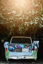 Vertical Blue Vintage Pick-up Truck Filled With Colorful Spring Flowers And Spring Decoration Decor For Home, Business Or Nursery With A Sunflare