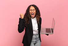 Young Hispanic Woman Shouting Aggressively With An Angry Expression Or With Fists Clenched Celebrating Success. Laptop Concept