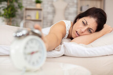 Woman Lying In Bed Suffering From Alarm Clock Sound