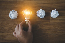 Hand Choose Light Bulb And Crumpled Office Paper. Concept Of Inspiration Creative Idea Thinking And Future Technology Innovation