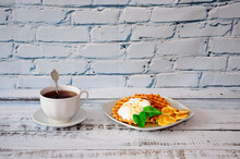 A Cup Of Black Tea On A Saucer With A Spoon And A Plate Of Waffles With Cream And Banana Pieces.