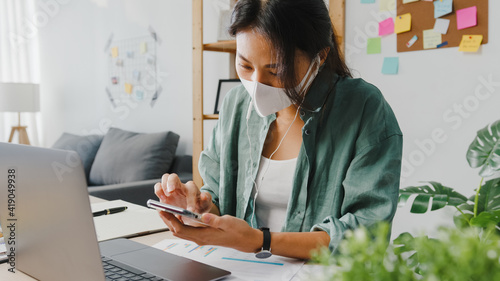 Obraz Freelancer Asia women wear face mask using smartphone shopping online via website while sitting at desk in living room. Working from home, remotely work, social distancing, quarantine for coronavirus. - fototapety do salonu