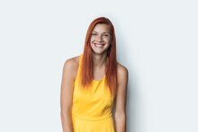 Adorable Ginger Woman With Nice Smile Is Looking At Camera Wearing A Yellow Dress On A White Studio Wall