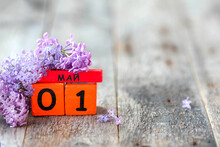 Wooden Calendar With Russian Text May 1 And A Bouquet Of Lilacs On A Wooden Background.Spring Day, Empty Space For Text. International Workers' Day