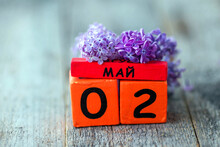 Wooden Calendar With Russian Text May 2 And A Bouquet Of Lilacs On A Wooden Background. Copy Space.