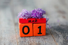 Wooden Calendar With Russian Text May 1 And A Bouquet Of Lilacs On A Wooden Background. Spring Day, Empty Space For Text. International Workers' Day