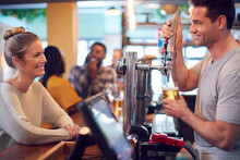 Smiling Male Bartender Behind Counter Serving Female Customer With Beer