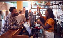 Smiling Female Bartender Behind Counter Serving Female Customer With Beer