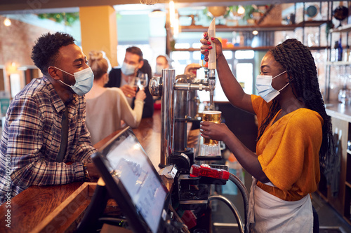 Female Bartender Wearing Face Mask Serving Male Customer With Beer During Health Fototapet