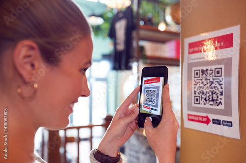 Woman With Mobile Phone Checking Into Venue Scanning QR Code During Health Pande Fototapet