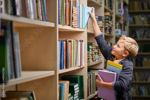 Fototapeta school boy taking books from shelves in library, with a stack of books in hands. child brain development, learn to read, cognitive skills concept obraz