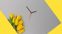 Yellow Tulips And Clock Hands On A 2021 Color Backdrop. Spring Time Change Concept.