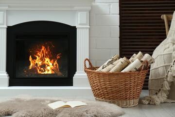 Firewood in wicker basket near fireplace indoors