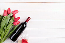 Bunch Of Colorful Tulips And Wine Bottle On White Wooden Background