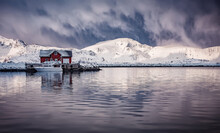 Wonderful Winter View On Snowcapped Mountains, Red Fishing Hut And Cloudy Sky With Reflection. Typical Nature Landscape Of Lofoten Islands. Norway. Travel Adventure And Freedom Concept.
