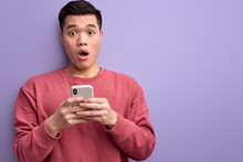 Emotional Asian Guy Chatting With Someone On Smartphone, Stand In Shock By News, Surprised By Message, Reacts On Something Looking At Camera. Isolated Purple Background
