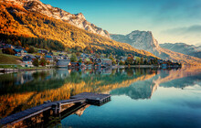 Stunning Nature Scenery, Amazing Beautiful Landscape View Of Rocks Hill In Sunny Mountains Over The Calm Water Of Grundlsee Lake. Beautiful Place Background. Travel, Adventure Concept.