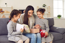 Happy Little Kids Making Surprise For Mommy. Cute Twin Daughters Giving Mom Presents And Card And Wishing Her Love And Happiness. Excited Young Woman Opens Gift Box Children Gave Her On Mother's Day