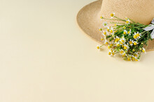 Beautiful Straw Hat With  Bouquet Of Daisies On Sand Sunny Day. Nature Summer Background.
