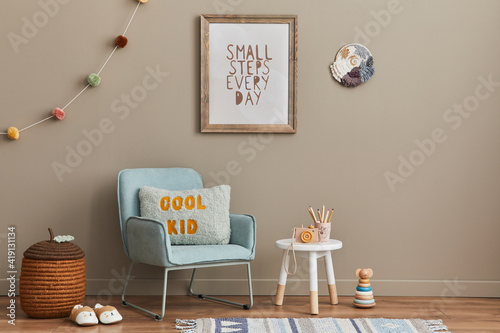 Cozy interior of child room with mint armchair, brown mock up poster frame, toys, teddy bear, plush animal, decoration and hanging cotton colorful balls Fototapeta