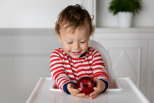 Smiling Baby In High Chair Holding Red Apple