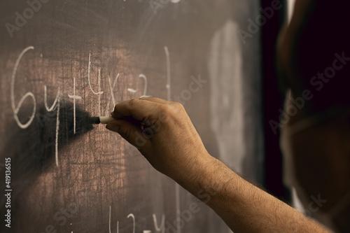Fotografia Teacher wearing mask writing equations on a blackboard