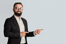 Serious Businessman In Office Wear Tand Glasses Smiling And Pointing Aside On Light Grey Background, Space For You Ad
