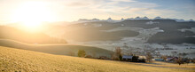 Sunrise Over The Hills Of Emmental With Bernese Alps In The Distance And Overlooking The Village Of Zäziwil
