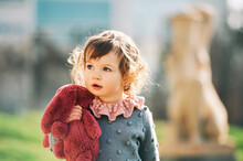 Outdoor Portrait Of Adorable Toddler Girl Playing Wirh Pink Bunny Toy