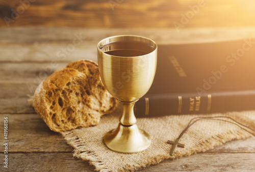 Chalice of wine with bread and Holy Bible on wooden background Fototapeta
