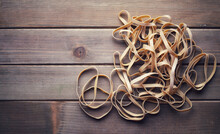 A Pile Of Rubber Bands On A Wooden Background