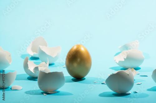 Fotografia Intact golden egg among broken white eggs