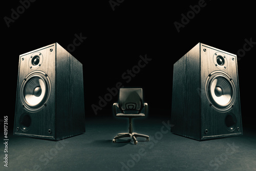 Photo Two sound speakers with office chair between them on black background