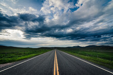 Road Heading Towards The Horizon On A Cloudy Day.