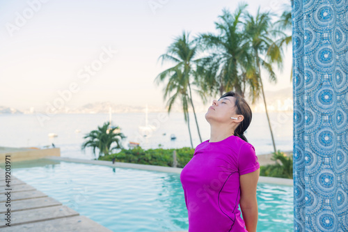 Woman practices yoga in front of the pool. Yoga poses outdoors.