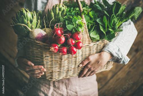 Fototapeta Woman farmer in linen apron holding basket of fresh organic garden vegetables and greens in hands, rustic wooden wall at background obraz