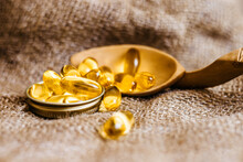 Fish Oil Capsules In A Wooden Spoon. Fish Oil Pills, Tablets On The Burlap. Vitamin Complex Omega 3,6,9. Fish Oil Capsules With Omega-3, Vitamin D. Top View. Copy Space