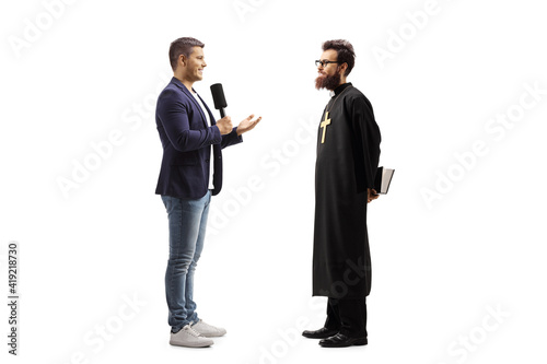 Fotografie, Obraz Full length profile shot of a reporter with a microphone talking to a catholic p