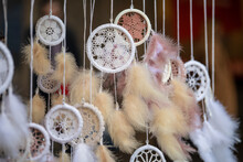 Close Up View Of Many Beautiful Dreamcatcher With A Lot Of Feathers, Hanging From A Ceiling Of Market Stall On Street. Handmade Knitted Dream Catcher. Street Market.