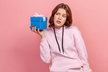 Portrait Of Funny Curious Brunette Teen Girl In Hoodie Holding Present Box Near Ear And Listening What's Inside, In Anticipation Of Dream Gift. Indoor Studio Shot Isolated On Pink Background