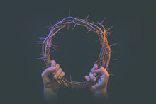 Two Hands Hold Crown Of Thorns
